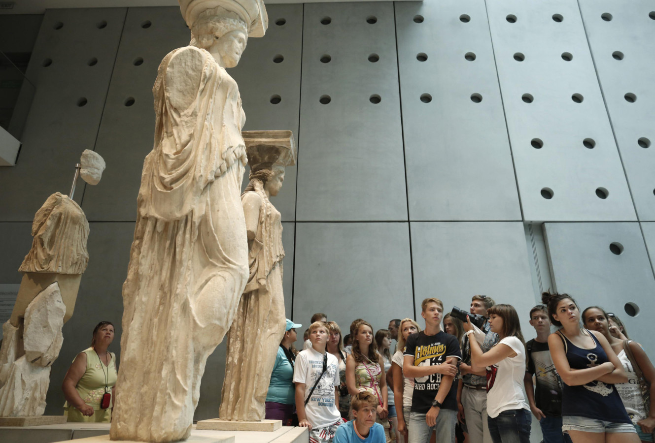 File photo shows tourists standing behind Karyatids statues at the Athens Acropolis Museum